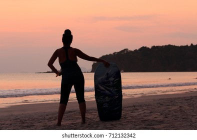 Woman surfing on the beach at sunset