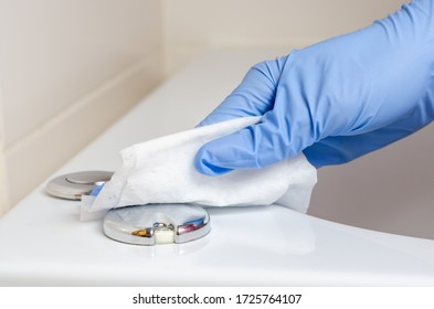 Woman with surgical gloves wiping the buttons on the jacuzzi bath with wet wipes .