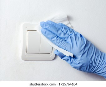 Woman with surgical gloves wiping and cleaning .  light bulb switcher . Bacteria   and covid-19    virus spreading  prevention  .