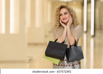 Woman surprise holds cheeks by hand .Beautiful girl with shopping bags pointing to looking left. Presenting your product. Expressive facial expressions