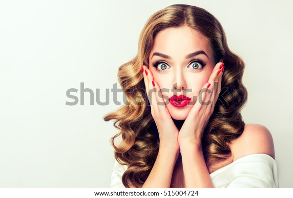Woman surprise holds cheeks by hand .Beautiful girl  with curly hair  pointing to looking right . Presenting your product. Isolated on white background. Expressive facial expressions