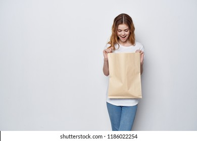 woman with surprise looks into a paper bag