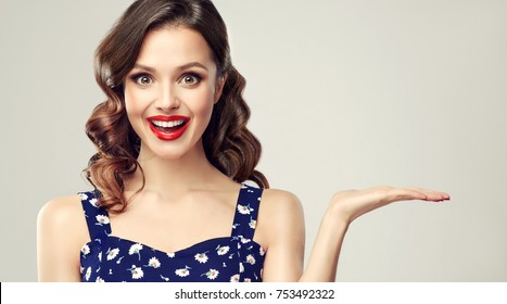 Woman surprise showing product .Beautiful girl  with curly hair and red lips pointing to the side . Presenting your product. Expressive facial expressions