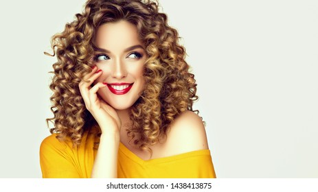 Woman surprise showing product with cunning look .Beautiful girl with curly hair looking away . Presenting your offer. Isolated on white background. Expressive facial expressions