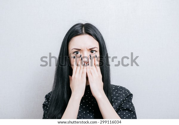 Woman surprised by covering her mouth with her hands. On a gray background.