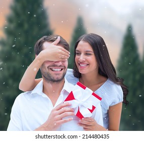 Woman surprising boyfriend with gift against fir tree forest