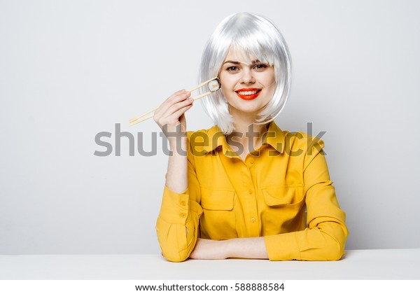 woman with sushi and rolls in hand..