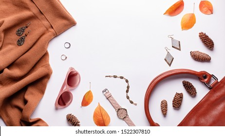 Woman sweater or dress with leather bag, jewelry, fashion accessories and autumn leaves. Autumn fashion background