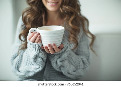 Woman in a sweater drinking tea