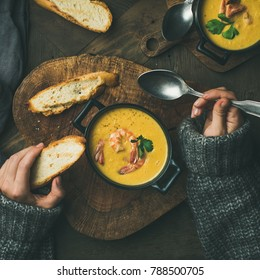 Woman in sweater eating corn creamy soup with shrimps in individual pot, top view, square crop. Woman' s hand with spoon and bread. Flat-lay of rustic table. Slow food, winter warming food concept