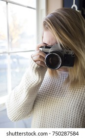 Woman in Sweater Takes Picture with Vintage Film Camera