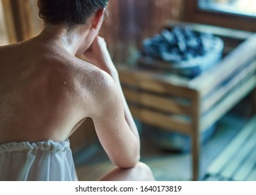 Woman sweating in Finnish sauna, steaming hot stone in the background.