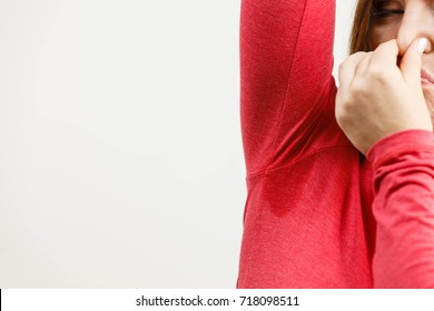 Woman sweating very badly have wet armpit, female holding her nose because of bad smell.