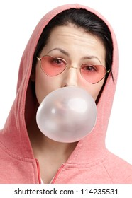 Woman in sweatshirt and heart shaped glasses blows out pink bubble gum, isolated on white