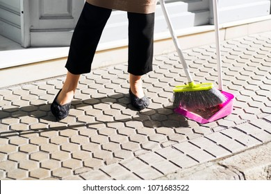 woman sweeping sidewalk for cleaner the street