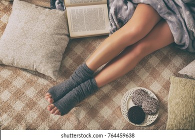 Woman with sweet gingerbread cookies, book lying on bed in the cozy room