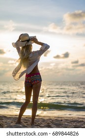 Woman in swiming suit posing on the beach at sunset