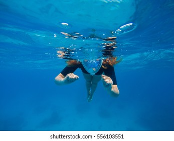 Woman swimming in blue water. Beautiful woman under water before dive to coral reef.  Half snorkel woman face in mask. Tropical sea snorkeling. Summer vacation activity. Woman snorkeling in blue sea.