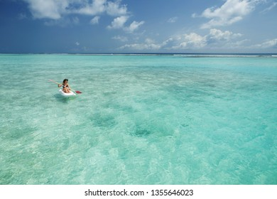 Woman swimming in canoe and relax in the sea. Happy island lifestyle. White sand, crystal-blue sea of tropical beach. Vacation at Paradise. Ocean beach relax, kayaking, travel to Maldives islands