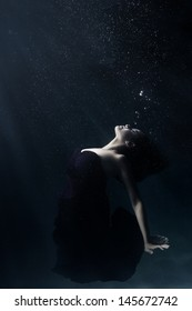 Woman Swimming in a Gown Underwater