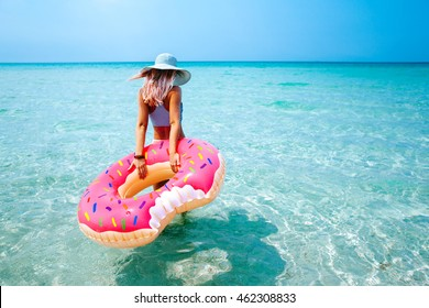 Woman swimming with inflatable donut on the beach in summer sunny day