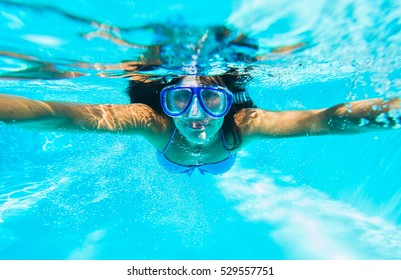Woman swimming with mask and blue bikini in swimming pool. Under waer shot.