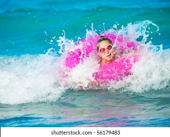 Woman swimming on innertube on the waves