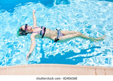 The woman is swimming in the pool