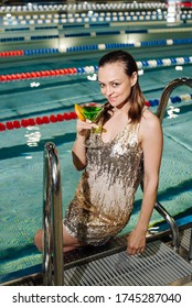 woman is in swimming pool, wearing cocktail dress with cocktail glass in her hand