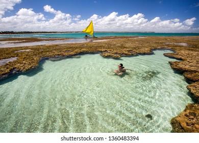 Woman swimming and relaxing on natural pool in Porto de Galinhas, Pernambuco - Brazil. Brazilian beach