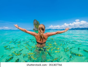 Woman swimming with snorkel surrounded by fish, Andaman Sea, Thailand