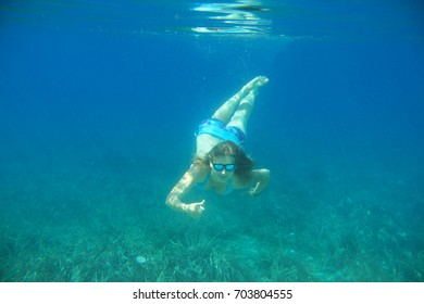 Woman swimming underwater in blue transparent sea water