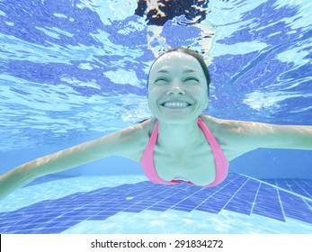 Woman swimming underwater in pool smiling