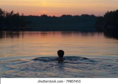 The woman swims in lake after sunset