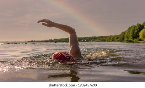 Woman swims in a lake in front of a rainbow