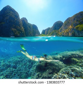 Woman swims snorkeling near colorful coral reef surrounded by a multitude of fish on the background Islands. Phi Phi island, Thailand.