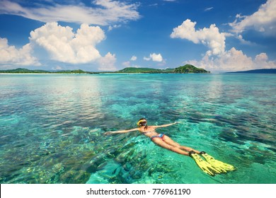 Woman in swimsuit is engaged snorkeling in transparent tropical sea above coral reef on the background islands.