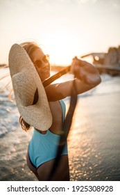 A woman in a swimsuit and a hat with glasses walks along the beach at sunset. The concept of sea recreation. Selective focus