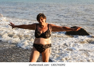 A woman in a swimsuit on the beach, fat deposits on the stomach and sagging skin.