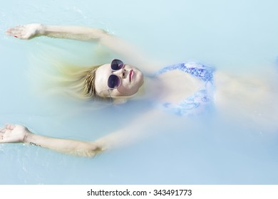 Woman in a swimsuit relaxing in the thermal pool of Blue Lagoon. Iceland