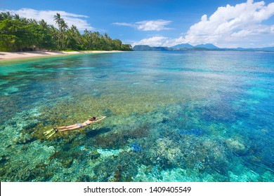 woman in swimsuit snorkeling in tropical sea above corals reef in sunny day. Island of Sulawesi. Indonesia