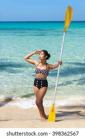 Woman in swimsuit standing on the beach with paddle in her hand. Asian woman in a retro swimsuit posing with paddle on a sea beach. Woman in retro style swimwear stands by the sea with paddle in hand.