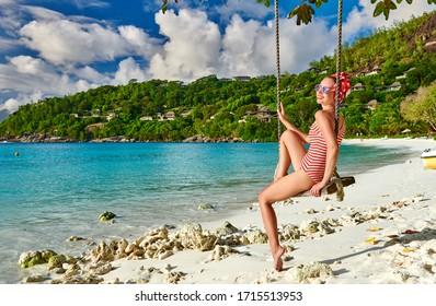 Woman swinging at tropical beach, Petite Anse, Mahe, Seychelles.