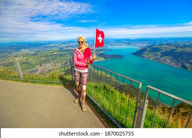 Woman with Swiss flag looking alpine panorama from Rigi-Kulm summit of Mount Rigi. Tourism in Canton of Lucerne, Central Switzerland. Amazing views and scenic landscape of popular tourist attraction.