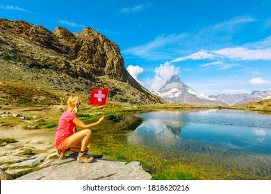 Woman with Swiss flag at Mount Matterhorn or Monte Cervino or Mont Cervin, reflected on Riffelsee Lake. Tourism in Zermatt,Canton of Valais, Switzerland.Scenic landscape of popular tourist attraction.