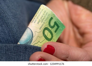 A woman and Swiss franc banknote in the pocket of a jeans