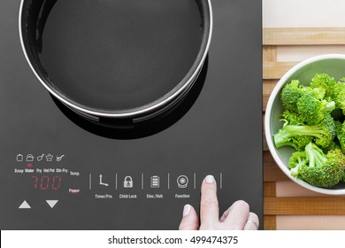 Woman switch on Induction stove and set power of heating, closeup