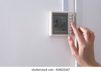 Woman switching a digital thermostat