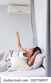Woman switching on air conditioner lying in bed