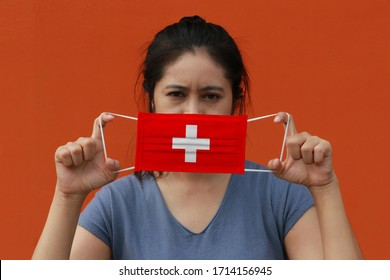 A woman with Switzerland flag on hygienic mask in her hand and lifted up the front face on orange color background. Tiny Particle or virus corona or Covid 19 protection. Concept of Combating illness.